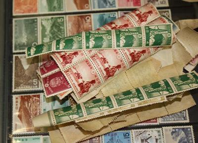 まるまってしまっている古い切手やコレクションの集まり